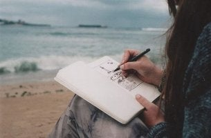 girl drawing on the beach