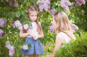 mother-speaking-to-angry-little-girl-among-flowers