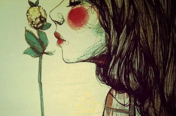 Kvinne lukter på blomst