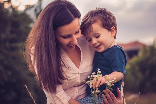 woman-holding-her-child-while-they-look-at-a-flower