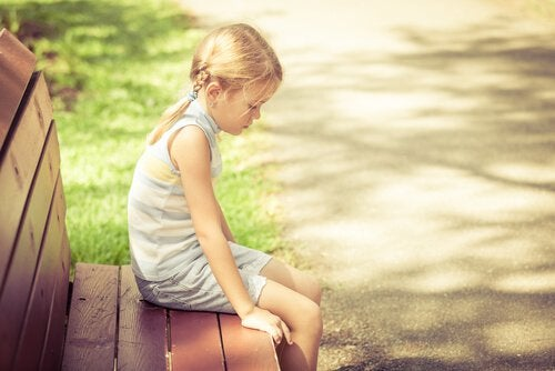 blonde-girl-sitting-on-a-bench-sad