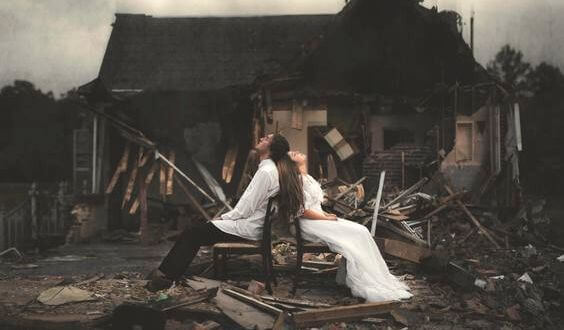 couple-in-front-of-a-destroyed-house