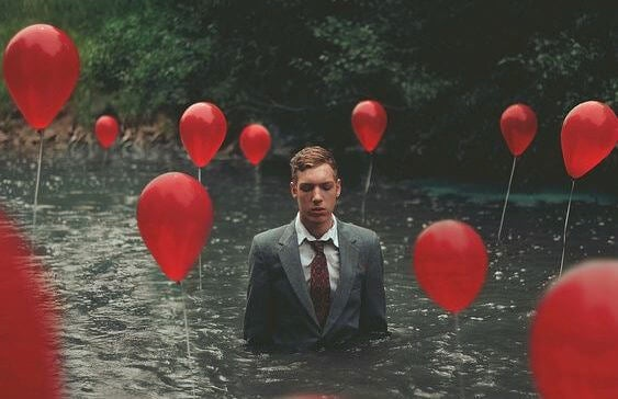 man in water with balloons