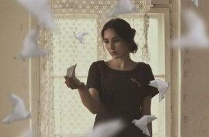 paper birds flying around woman