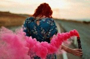 woman holding pink smoke