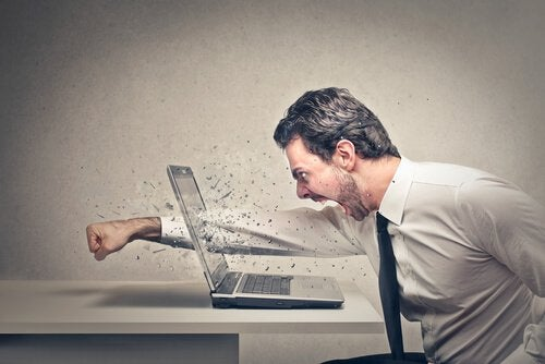angry man punching through a laptop screen