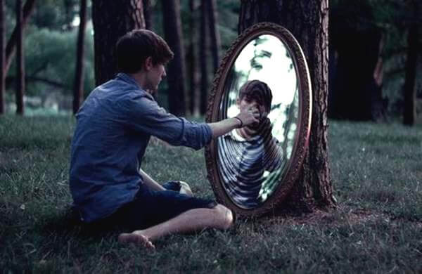 boy touching mirror in woods