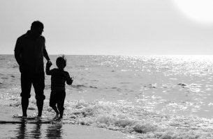 father and son walk along the beach