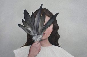 girl covering face with feathers
