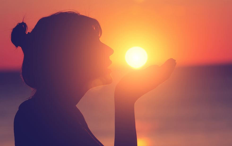 silhouette of girl holding sun at sunset