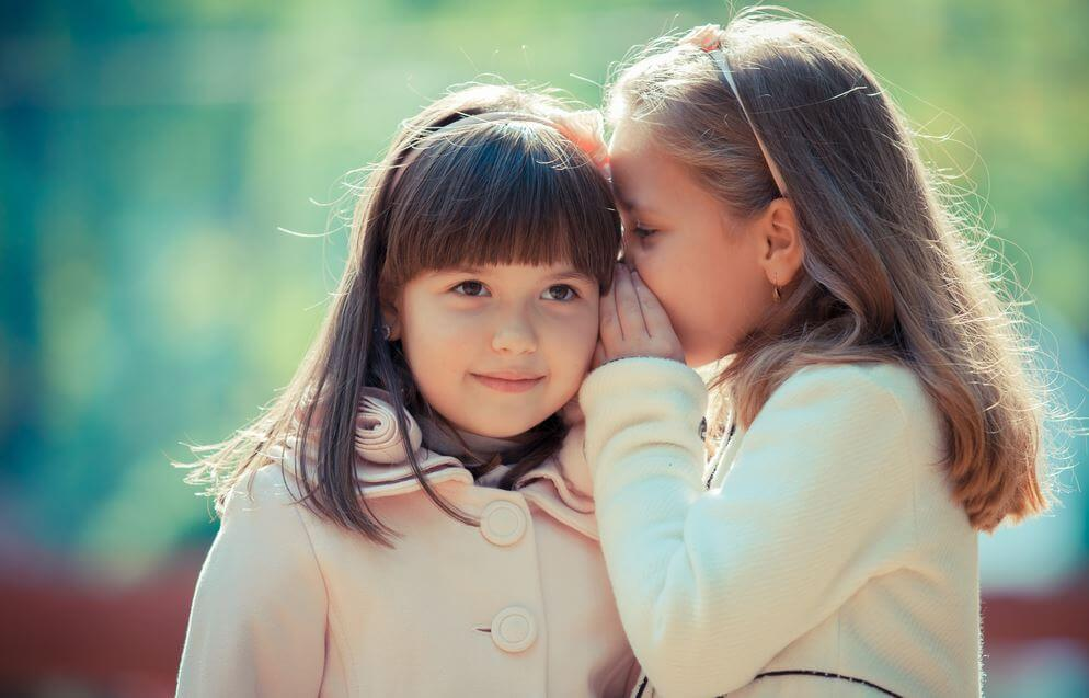 small girl whispering secret to her friend