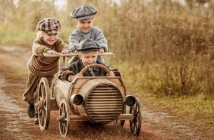three small boys playing with a cart