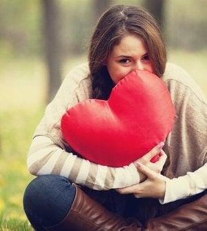 woman holding heart pillow