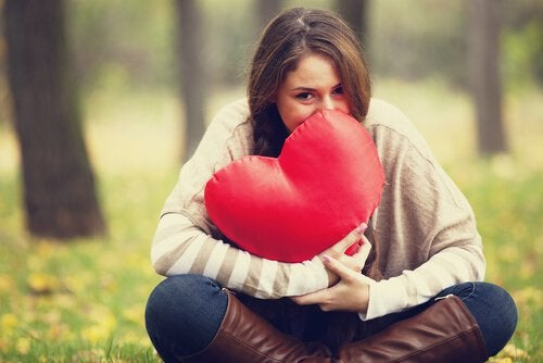 woman holding heart pillow