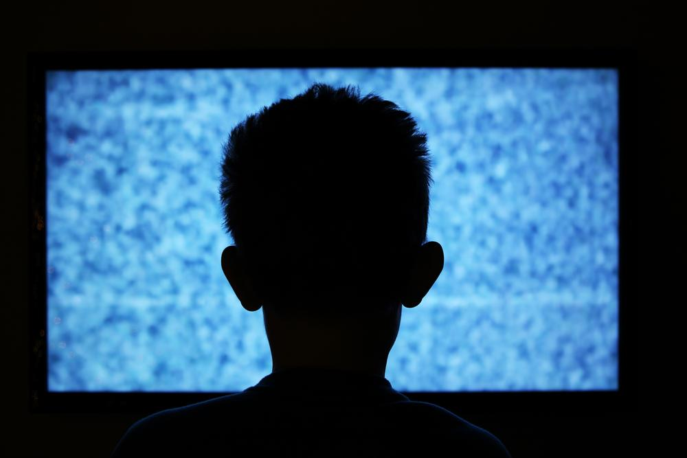 child in front of static tv