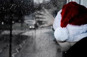 child with santa hat looking out window