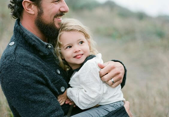 little girl being hugged by her father