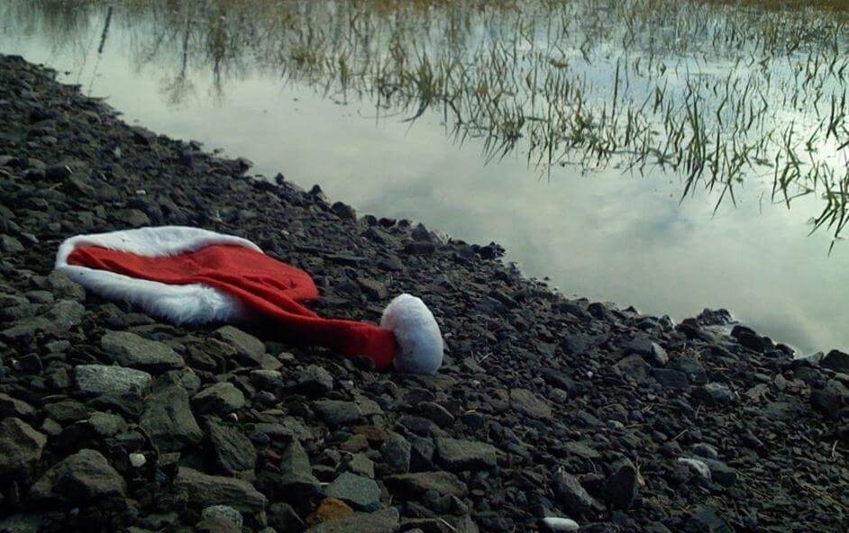 santa hat on the ground by a river