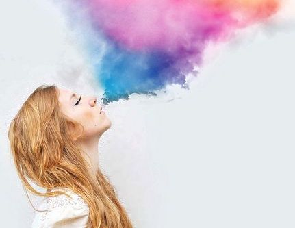 girl blowing out colorful smoke