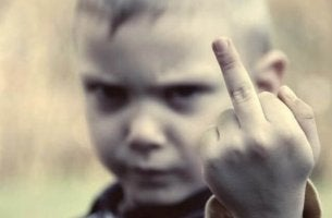 An angry kid is flipping the middle finger at the camera.