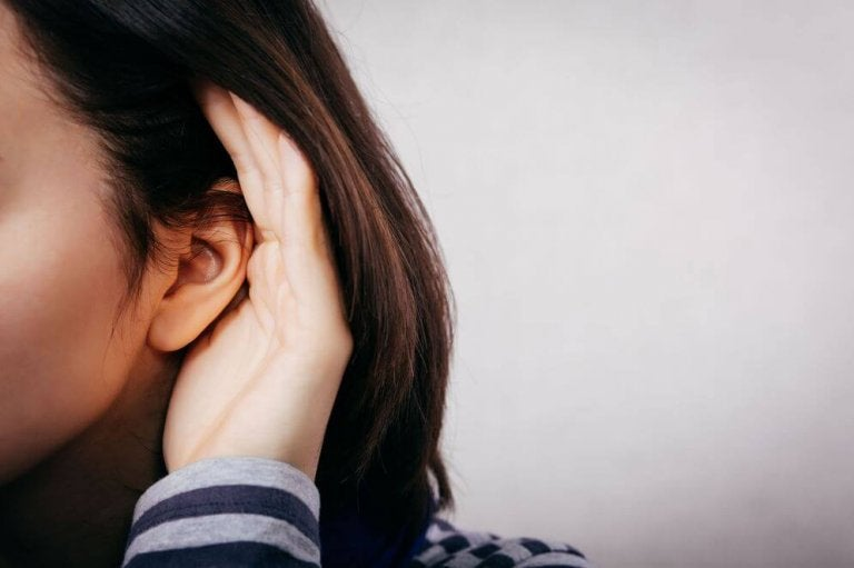 A woman is cupping her ear to hear the limits.