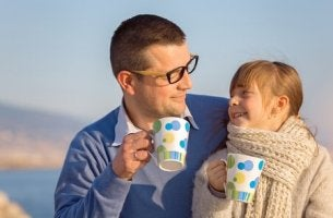 father and daughter holding matching cups
