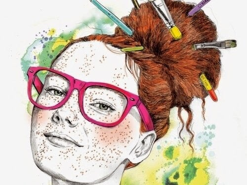 A girl with many freckles has paint brushes in her red hair.