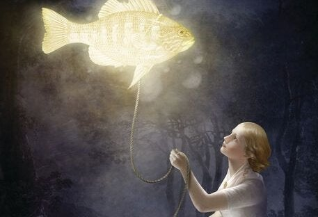 A girl has a glowing floating fish on a leash.