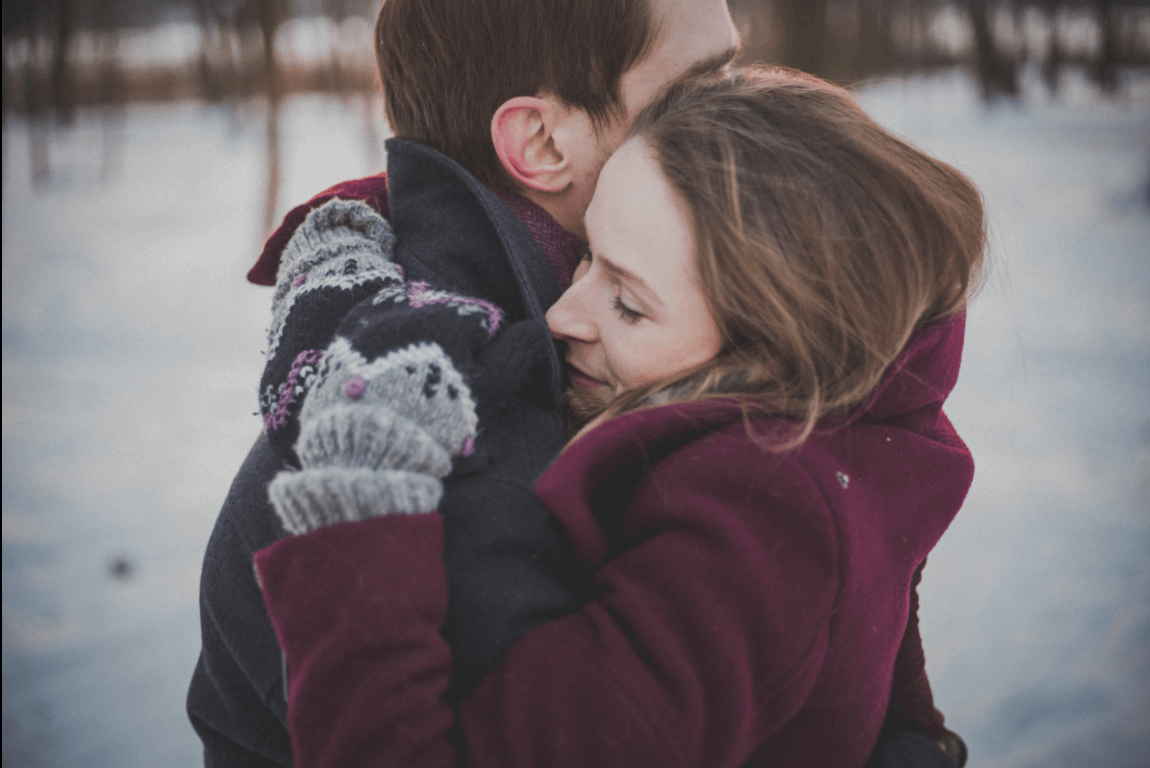 A happy couple in a hug in a snowy field.