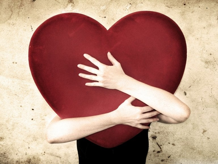 A person is hugging a giant heart.