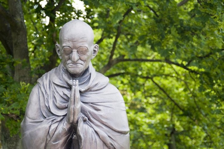 A statue of Gandhi praying.