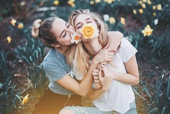 two girlfriends with flowers in their mouths