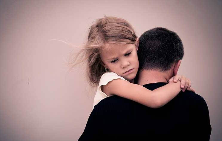 upset girl being carried by father