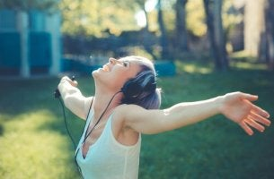 A woman is listening to music with her arms in the air.