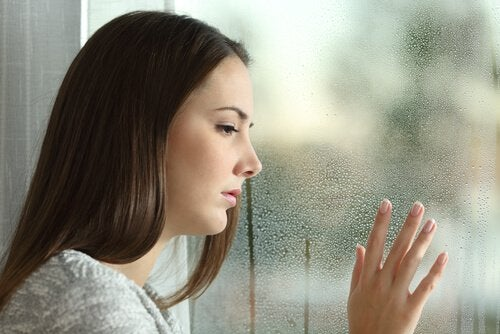 woman staring out rainy window