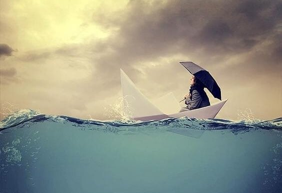 A woman with an umbrella is sailing in a paper boat.
