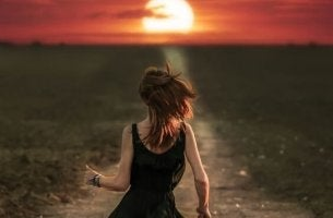 A girl is running towards the sunset.