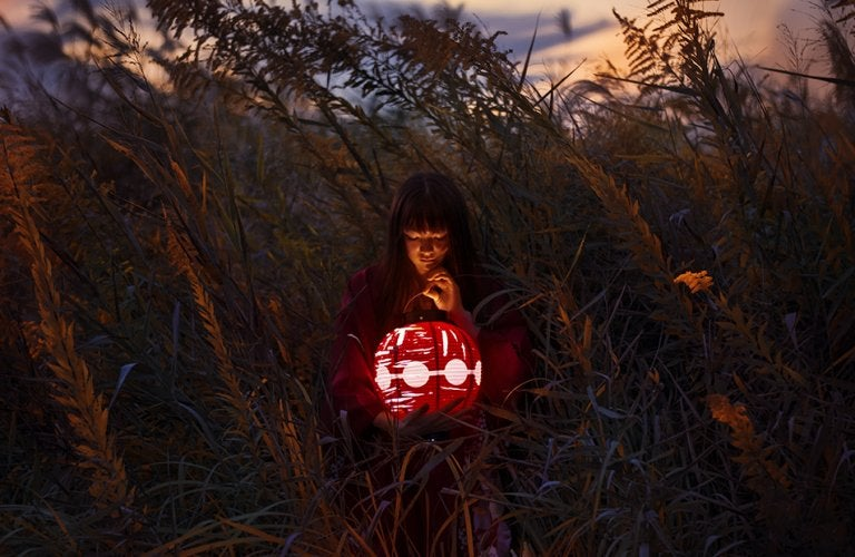 A Japanese girl with a lantern in a field.