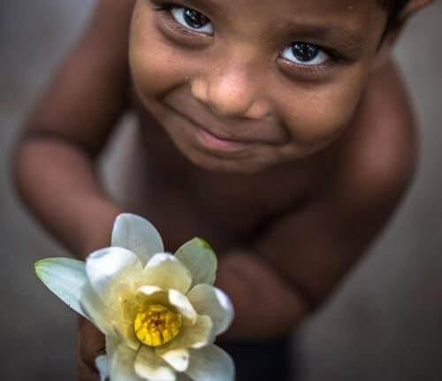 a grateful boy smiling and holding a flower