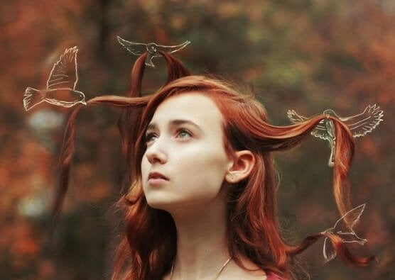 a girl with red hair being held up by white birds