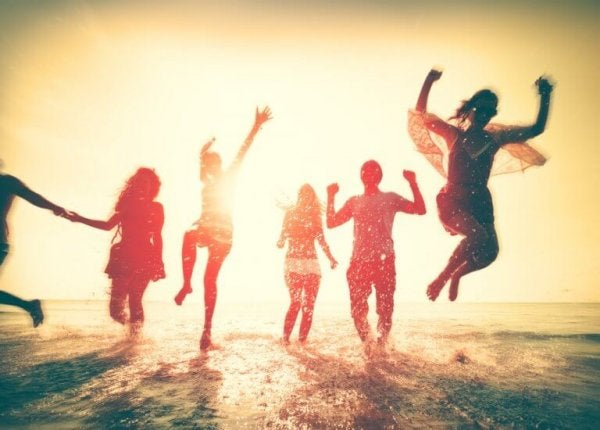 friends jumping happily in the waves
