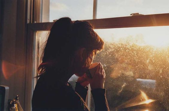 a woman looking out the window with coffee