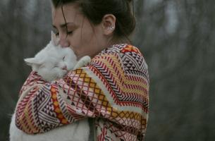 A woman hugging a cat.