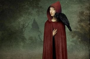 A woman stands in a red hood with a crow on her shoulder.