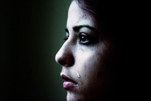 A sad girl has a tear drop falling down her cheek.