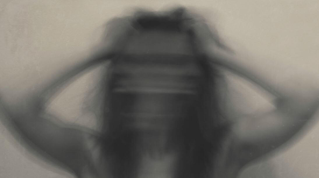 a blurry woman with her hands to her head in anxiety