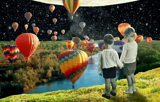 two kids holding hands watching hot air balloons