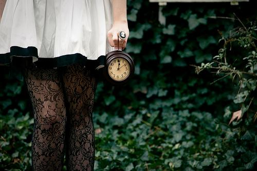 a girl holding a clock