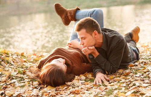 A couple in a new relationship laying in fall leaves next to a lake.