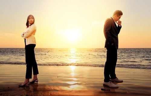 a couple fighting on the beach in formal clothes